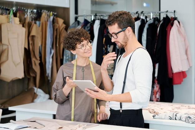 Junge modedesigner diskutieren details neuer digitaler skizzen für ihre modekollektion im touchpad