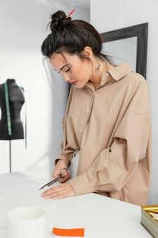 Junge modedesignerin arbeitet allein in ihrer werkstatt