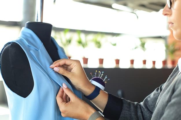 Junge modedesignerin arbeitet in ihrem atelier an neuen tüchern.