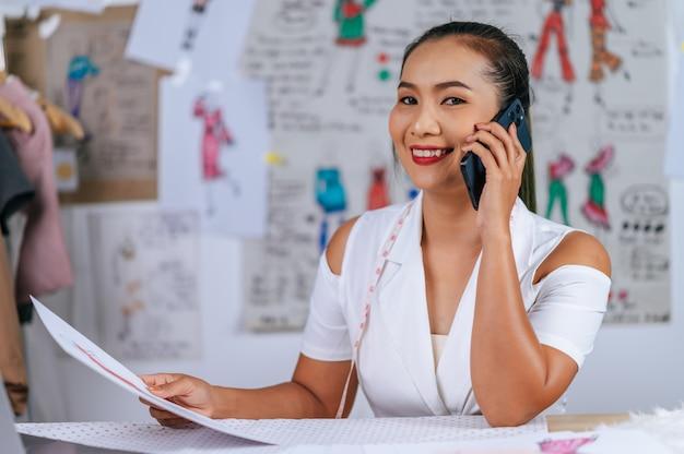 Junge modedesignerin, die mit smartphone spricht und auf kleidungsskizze schaut