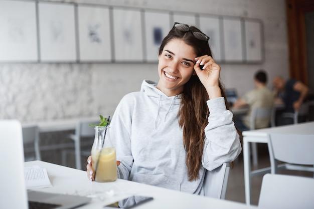 Junge modedesignprofi, die eine pause von ihrer harten arbeit macht, limonade trinkend lächelnd musik im geräumigen offenen coworking center hörend.