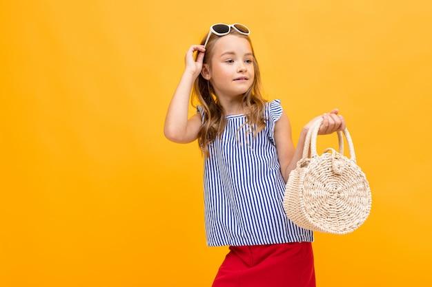 Junge modefan mit einer runden nachtigallhandtasche und einer brille auf ihrem kopf, die auf einer leuchtend gelben wand aufwirft