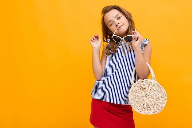 Junge modefanatikerin mit einer runden nachtigallhandtasche und einer brille auf dem kopf, die gegen eine leuchtend orange wand posiert
