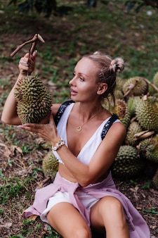 Junge modefrau auf einem tropischen feld mit durianfrüchten