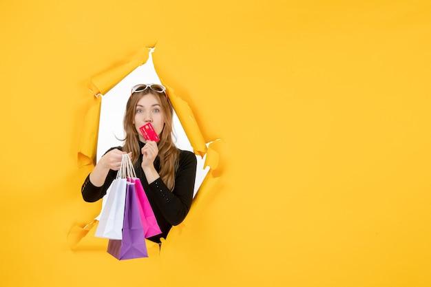 Junge modefrau, die einkaufstaschen und kreditkarte durch zerrissenes papierloch in der wand hält