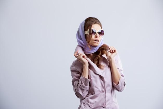 Junge modefrau, die im studio trägt rosa mantel und weiße sonnenbrille aufwirft