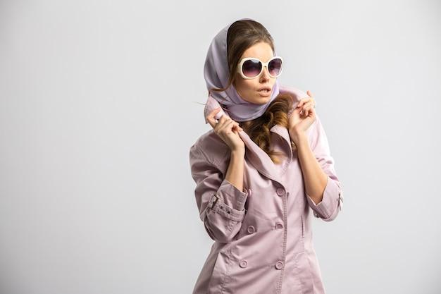 Junge modefrau, die rosa mantel und weiße sonnenbrille tragend aufwirft