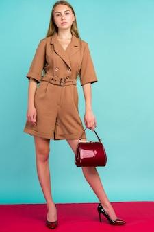 Junge modefrau halten handtaschenkupplung lokalisiert auf blauem raum