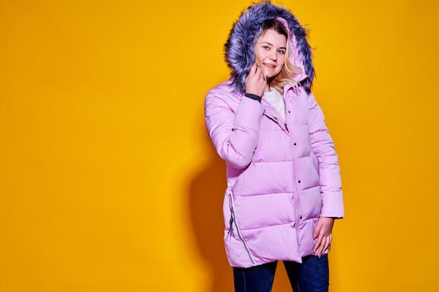 Junge modefrau in der kurzen violetten daunenjacke