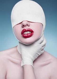 Junge modefrau mit den verbundenen kopf- und krankenschwesterhänden