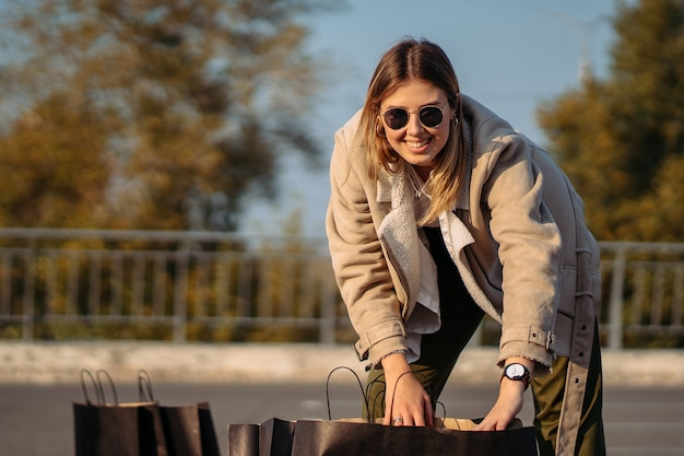 Junge modefrau mit einkaufstaschen auf dem parkplatz