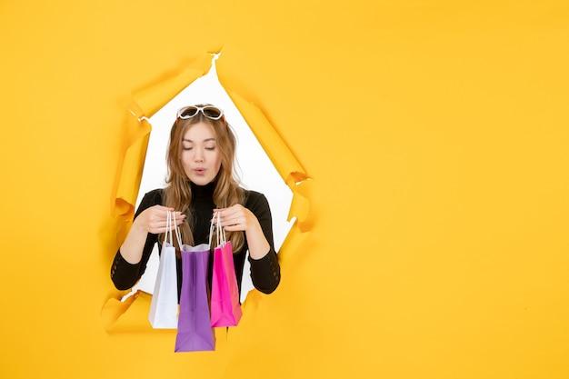Junge modefrau mit einkaufstüten durch zerrissenes papierloch in der wand