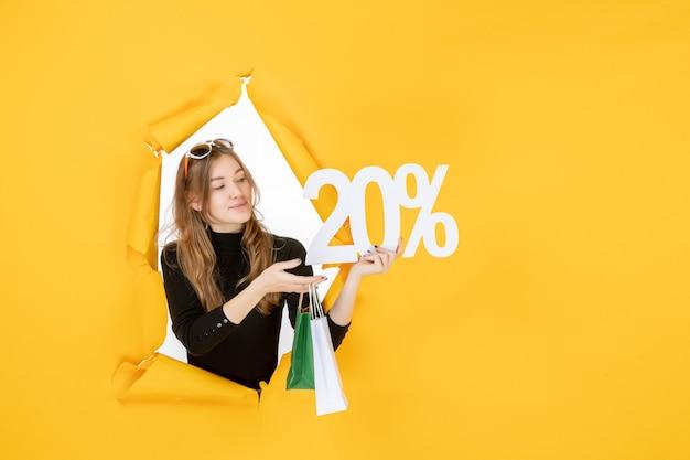 Junge modefrau mit einkaufstüten und rabattprozentsatz durch zerrissenes papierloch in der wand