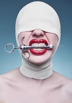 Junge modefrau mit verbundenem kopf und injektor