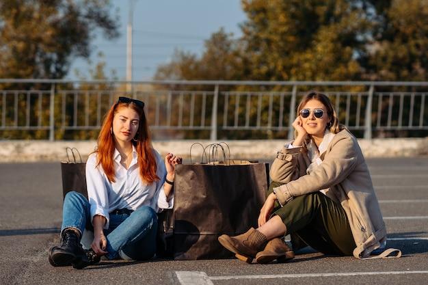 Junge modefrauen mit einkaufstaschen sitzen auf dem parkplatz