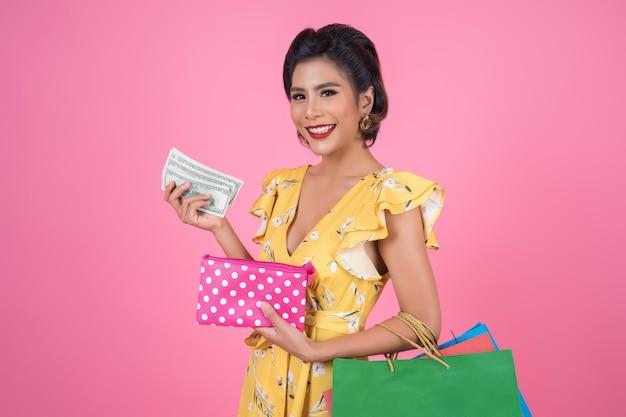 Junge modefrauenhand, die geldbörse und einkaufstaschen hält