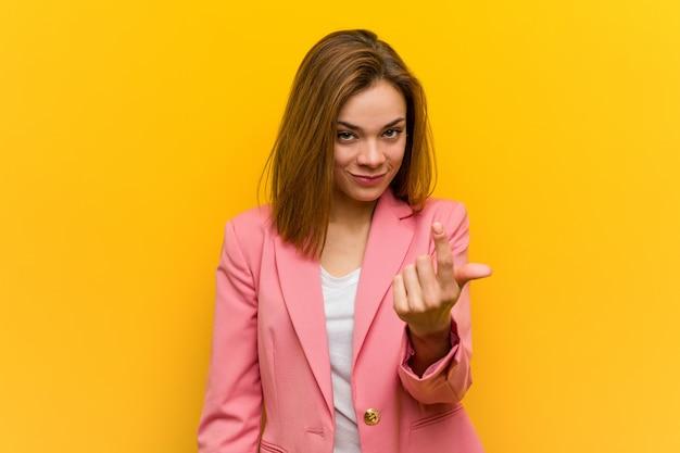 Junge modegeschäftsfrau, die mit dem finger auf sie zeigt, als ob einladung näher kommen.