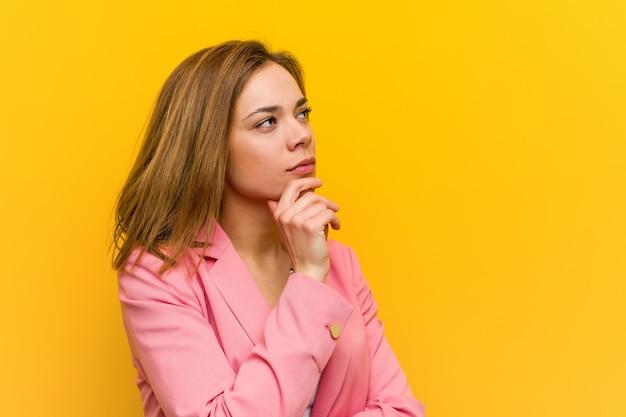 Junge modegeschäftsfrau, die seitlich mit zweifelhaftem und skeptischem ausdruck schaut.