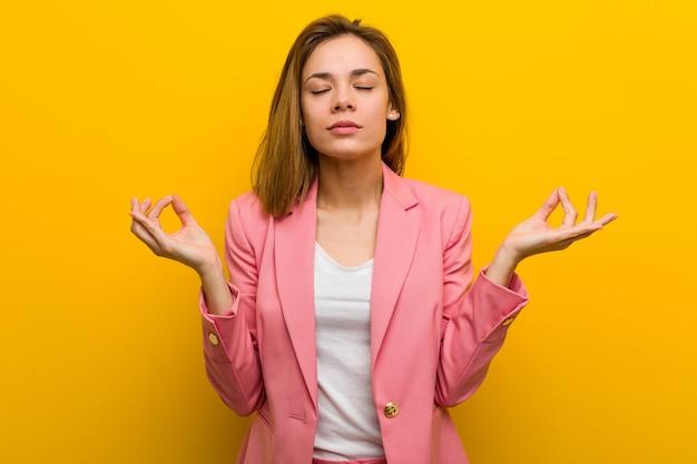 Junge modegeschäftsfrau entspannt sich nach hartem arbeitstag, sie führt yoga durch.