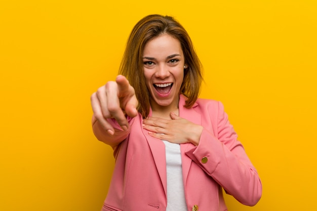 Junge modegeschäftsfrau zeigt mit dem daumenfinger weg, lachend und sorglos.