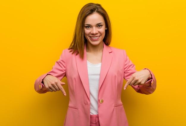 Junge modegeschäftsfrau zeigt unten mit den fingern, positives gefühl.