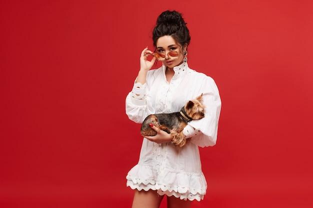 Junge model frau mit lockigen schwarzen haaren in modischer sonnenbrille und weißem kleid hält ein yorkshire ...