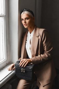 Junge modelfrau mit blonden haaren in einem modischen anzug posiert mit einer trendigen handtasche im vintage-interieur in der nähe des fensters