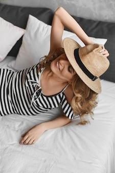 Junge modelfrau mit schlankem perfekten körper trägt einen gestreiften body und einen sommerhut posiert auf dem bett...