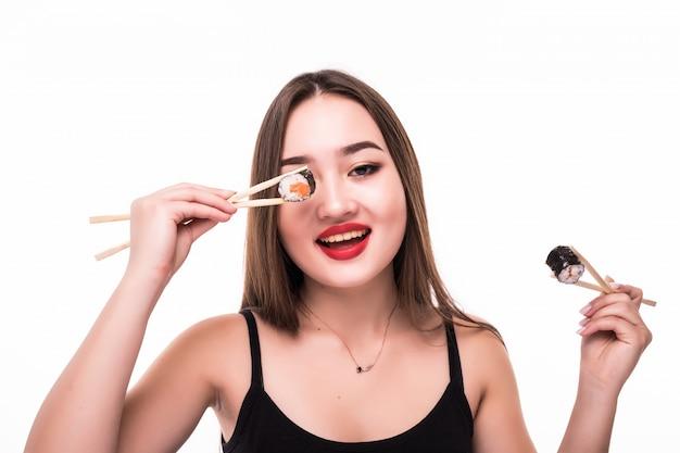 Junge modell asiatischen blick bedecken ihre augen mit sushi-rollen halten mit hölzernen essstäbchen