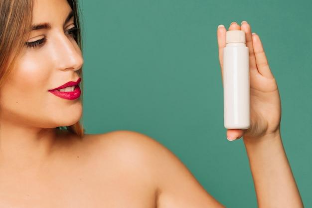 Junge modell posiert mit kosmetischen produkt