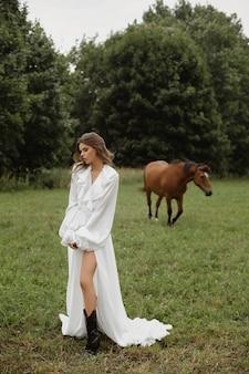 Junge modellfrau mit perfektem schlanken körper im langen weißen kleid, das mit einem braunen pferd auf der grünen sommerwiese aufwirft