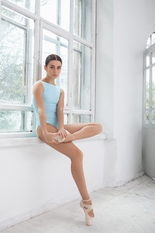 Junge moderne balletttänzerin posiert auf weiß
