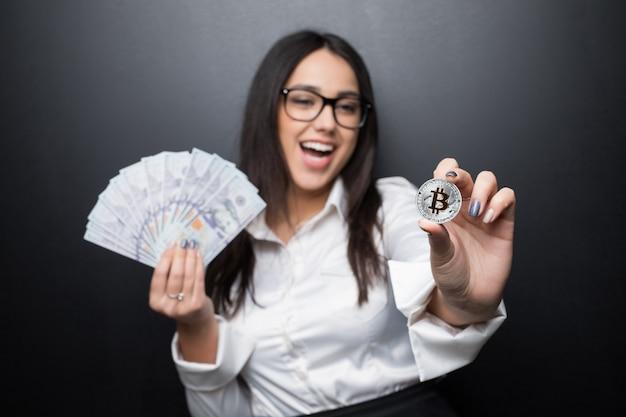 Junge moderne erfolgreiche geschäftsfrau, die eine goldene bitcoin und bargelddollar lokalisiert auf schwarzer wand hält