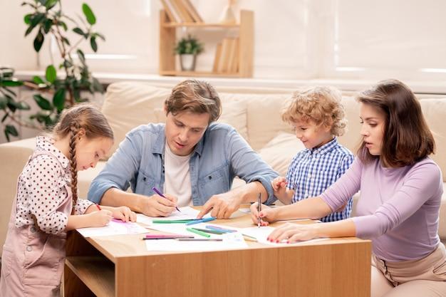 Junge moderne familie des verheirateten paares und ihrer zwei kleinen kinder im grundschulalter, die bilder mit textmarkern oder buntstiften zu hause zeichnen