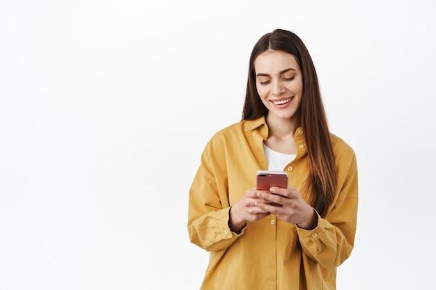 Junge moderne frau, die am telefon chattet, den smartphone-bildschirm mit unbeschwertem lächeln liest, sms schreibt oder in der online-shop-app surft und gegen die weiße wand steht