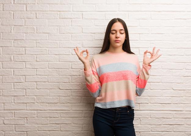 Junge moderne frau, die yoga durchführt