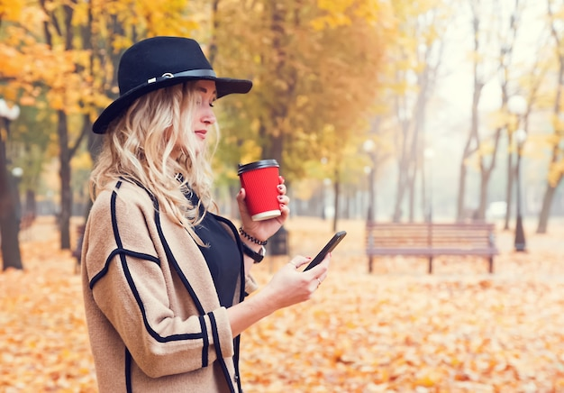 Junge moderne frau im herbstpark, der pappbecher mit kaffee und sms mit ihrem smarphone hält