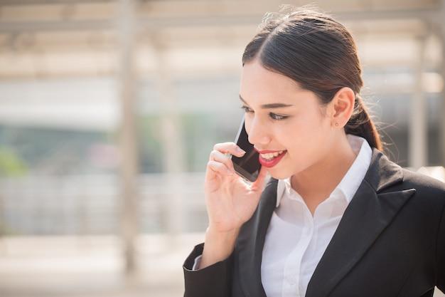 Junge moderne geschäftsfrau, die intelligentes telefon mit kopienraum verwendet