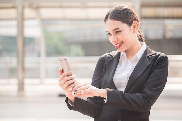 Junge moderne geschäftsfrau mit telefon