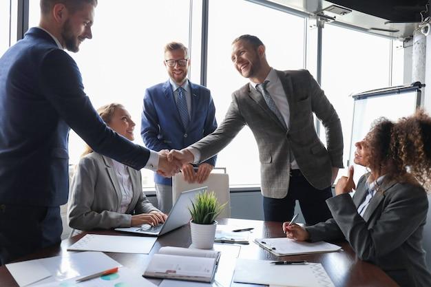 Junge moderne geschäftsleute in formeller kleidung, die hände schütteln und lächeln, während sie im büro arbeiten.