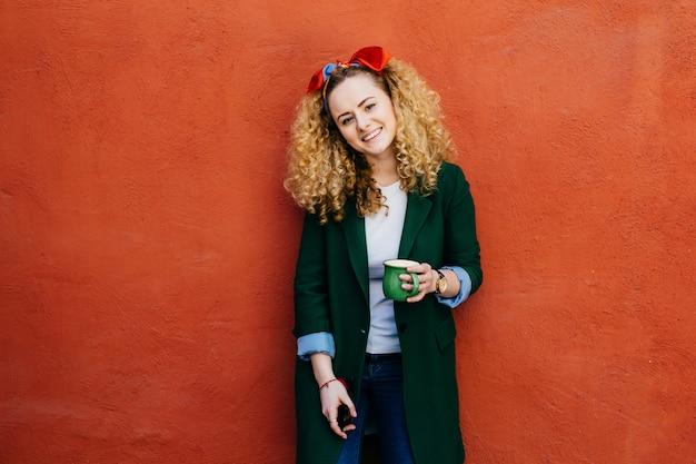 Junge moderne kaukasische frau mit tragendem stirnband des gelockten haares und stilvoller jacke.