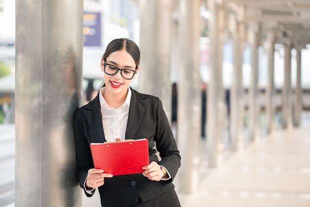 Junge moderne lächelnde geschäftsfrau, die karton mit kopienraum sucht