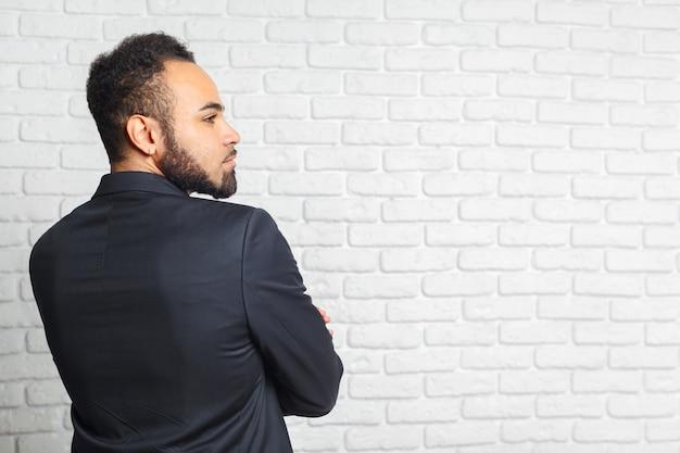 Junge moderne männer in einer klage gegen backsteinmauer