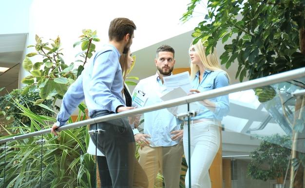 Junge moderne menschen in smarter freizeitkleidung, die ein brainstorming treffen, während sie hinter der glaswand im büro stehen.