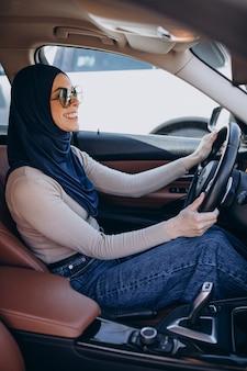 Junge moderne muslimische frau, die im auto fährt