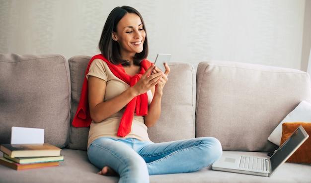 Junge moderne selbstbewusste lächelnde frau arbeitet oder entspannt zu hause und sitzt auf der couch, während sie ihr smartphone benutzt