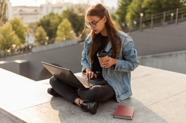 Junge moderne studentin in einer jeansjacke, die auf der treppe mit laptop sitzt. fernunterricht. modernes jugendkonzept.
