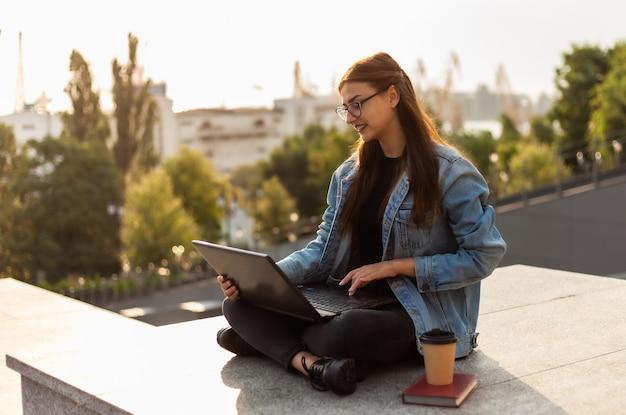 Junge moderne studentin in einer jeansjacke sitzend und verwendet laptop im freien. fernunterricht. modernes jugendkonzept.