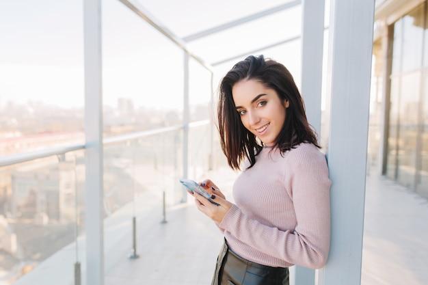 Junge modische brünette frau des stilvollen stadtporträts, die telefon auf terrasse auf stadtansicht verwendet. attraktive geschäftsfrau, fröhliche stimmung, lächelnd.