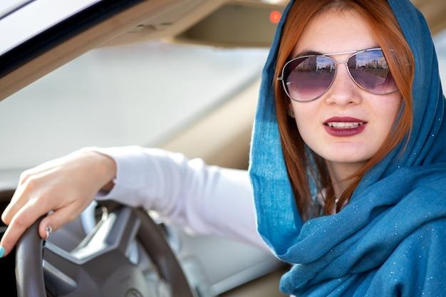 Junge modische fahrerin im schal und in der sonnenbrille, die ein auto fahren.